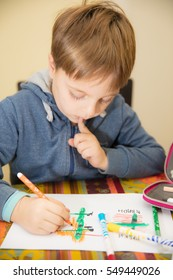 Little boy sitting at the table at home, drawing with colored pencils, having fun.
