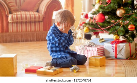 Little boy sitting under Christmas tree and crying