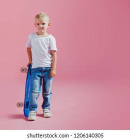 little boy with a skateboard. Beginner skater, pink background