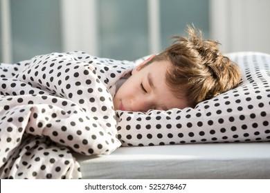 Little boy sleeping in bed