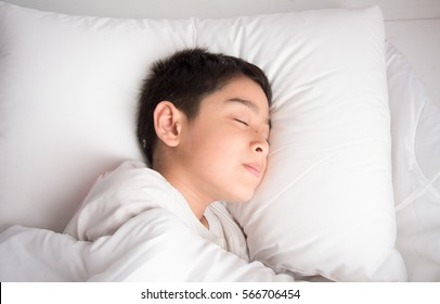 Little boy sleeping in the bed on  with white blanket cover