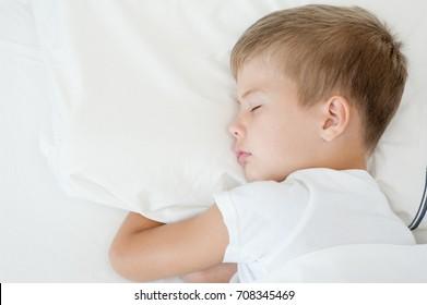 Little boy sleeping in bed. Top view