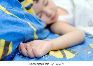 A little boy is sleeping in his bed