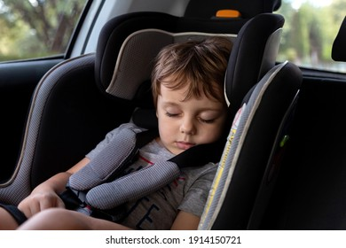 Little boy sleeping on the harness booster seat into a car. Security seat for children.