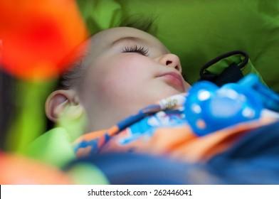 Little boy is sleeping in the stroller outdoors