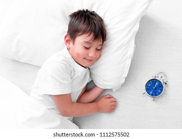 Little boy sleeping in white bed with small alarm clock