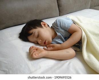 little boy sleeps in bed