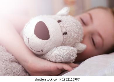 A little boy sleeps with a white bear, a cute baby. So close.