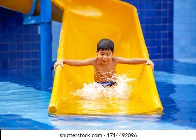 little boy sliding on the swimming pool