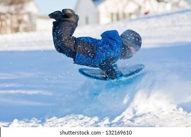 Little boy sliding in the snow