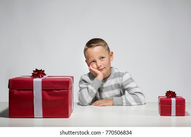 Little boy with a small an a big Xmas-present is dreaming in front of white background