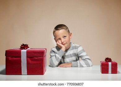 Little boy with a small an a big Xmas-present is dreaming in front of colored background