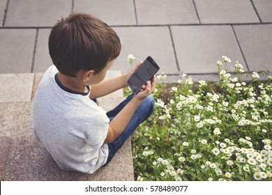 Little boy with smartphone sitting on stairs in city park. Technology, education and lifestyle concept