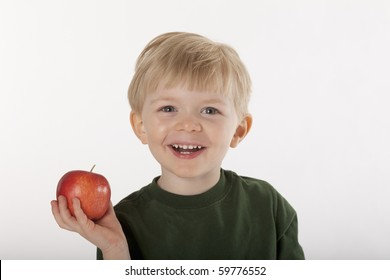 Little boy smiles at the camera while holding an apple in one hand. Horizontal shot.