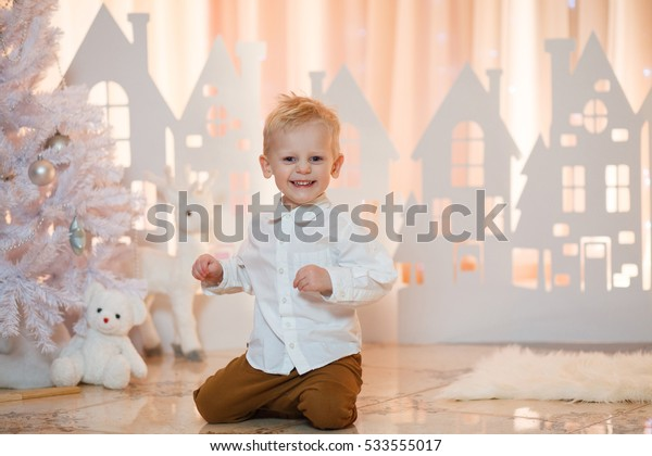 Little boy smiles on a background paper houses. White christmas. Selective focus