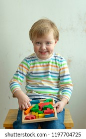 Little boy smiles and plays with wooden puzzle