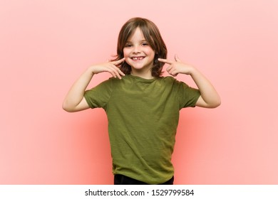 Little boy smiles, pointing fingers at mouth.