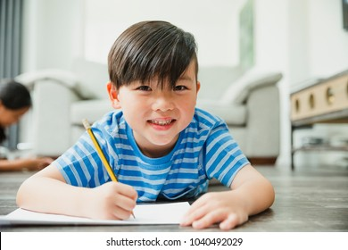 Little boy is smiling for the camera while lying on the floor as he is doing his homework.
