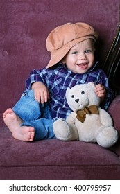 Little boy smiling. He is happy. Baby sitting on the couch in his hands a toy teddy bear
