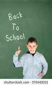 Little boy smiling on a green board background. Pointing his finger up to :  Back to School