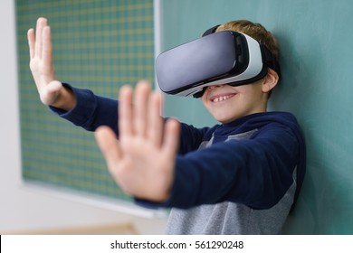 Little boy smiling wearing virtual reality 3D helmet leaning back on classroom chalkboard and spreading his arms with palms up