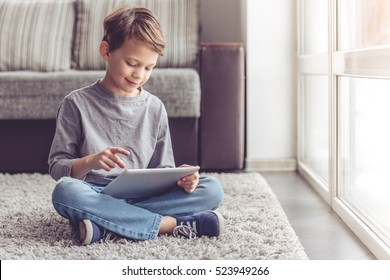 Little boy is smiling while playing with digital tablet at home