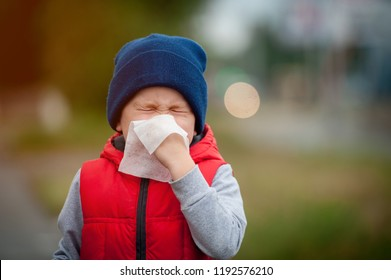 Little boy sneezing with tissue outdoors. Sick child with napkin in autumn park. Allergic kid, flu season. Kid with cold rhinitis