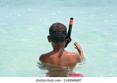 Little boy snorkeling in crystal clear water