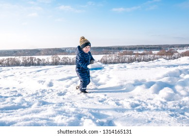 Little boy with a snow shovel in the winter in the park. Happy carrying snow on a shovel in casual clothes.