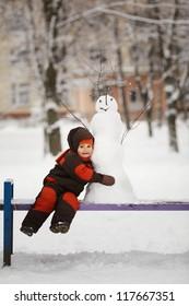 little boy with snowman
