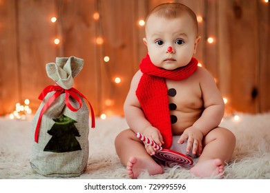 little boy in a snowman costume sitting near a bag with a Christmas tree