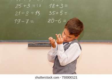 A little boy solves mathematical examples of standing at blackboard.