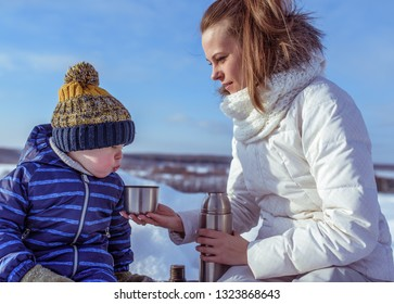 Little boy son 3-5 years old, sitting on bench winter in city. The concept of caring for support healthier eating in nature on a snowy winter day. Woman mom holding thermos with a hot soup drink.