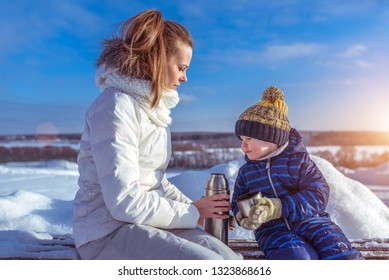 Little boy son 4-6 years old, sitting on bench winter city. Woman mom holding thermos with a hot soup drink. The concept of caring for support healthier eating in nature on a snowy winter day.