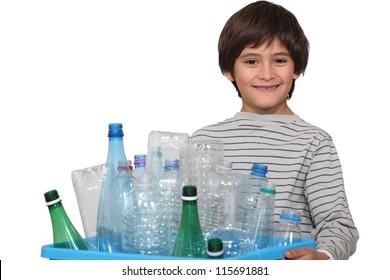Little boy sorting plastic bottles for garbage