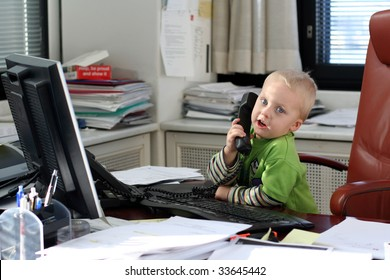 Little boy speaking on phone in the office