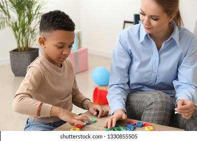 Little boy with speech therapist composing words of letters in office