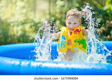 Little boy is splashing in inflatable swimming pool outdoor, having fun.Yellow  swimming aids on child in garden sunshine