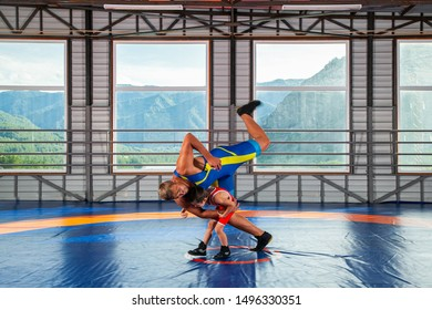 The little boy in sport tights wrestler throws over the hip adult male wrestler on a wrestling carpet in the gym. The concept of child  martial arts training. Teaching children Greco-Roman wrestling