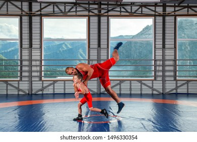 The little boy in sport tights wrestler throws over the hip adult male wrestler on a wrestling carpet in the gym. The concept of child power and martial arts training. Teaching Greco-Roman wrestling
