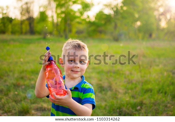 little boy with a spray on a meadow