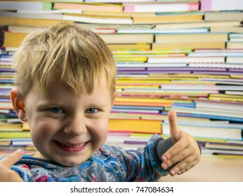 The little boy spread his fingers against the background of a large number of colorful books.