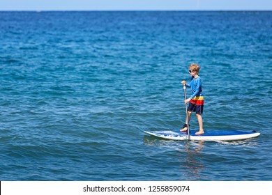 little boy stand up paddleboarding alone, enjoying active vacation at lanai island, hawaii, copy space on left
