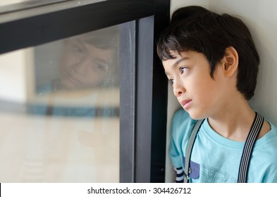Little boy standing behind the window with sad face
