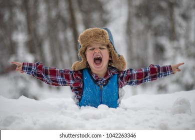 A little boy is standing in a deep snow bank after a snow storm. He has a furry winter hat with ear flaps and a plaid shirt with snow pants. The child thinks the deep snow is fun and is laughing.