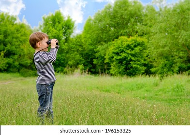 Little boy standing in a green grassy field scanning the surrounding woods with binoculars as he explores the countryside