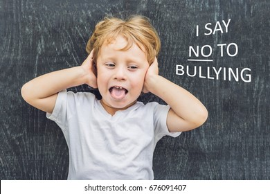 Little boy standing up for himself and saying NO to bullying by blowing a raspberry at the bully in front of a blackboard at school.