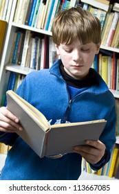 Little boy  standing near the bookshelf