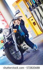 little boy standing near a motorcycle at a gas station