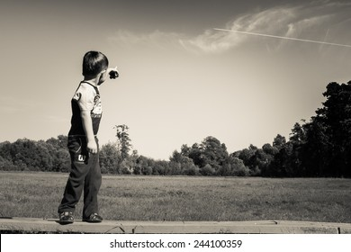 Little Boy Standing On Bench And Pointing At Flying Plane In  Summer Sky